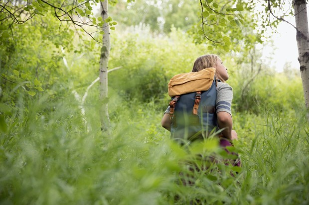 Curious teenage girl with backpack hiking in tall grass in woods