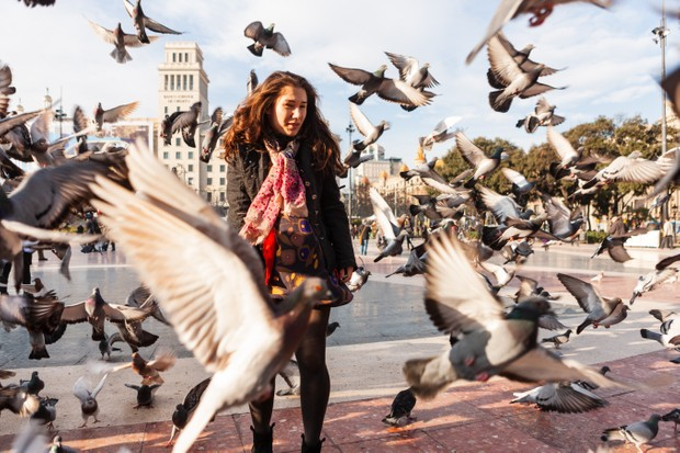 Young woman in the middle of a flock of pigeons in Barcelona