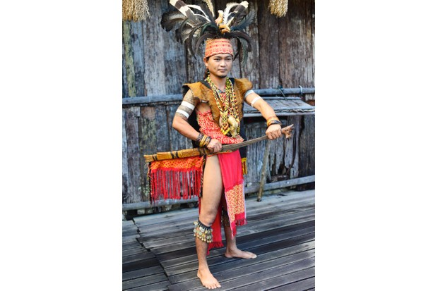 A young Iban man in warrior headhunter regalia, including hornbill feather headdress, at Sarawak Cultural Village.