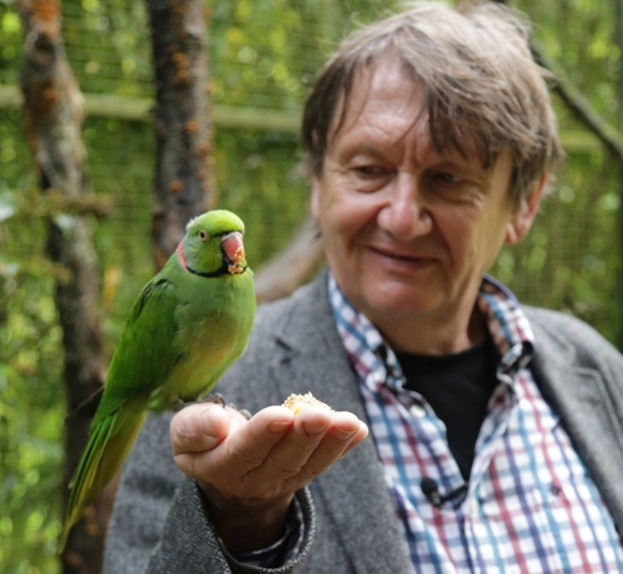 Dr Carl Jones with an echo parakeet, one of the species he saved from extinction.