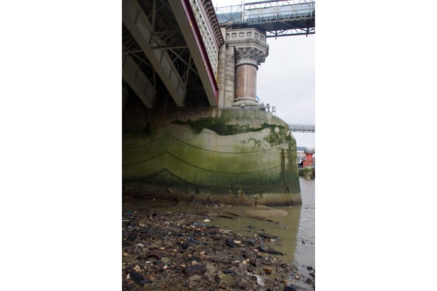 Pylon of Blackfriars Bridge at low tide on the River Thames, foreshore strewn with rusted metal, plastic, building rubble and other trash. © Simon McGill/Getty