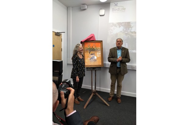 Wildlife artists Carrie Aykroyd and Birdfair founder Tim Appleton with the poster for Birdfair 2019.