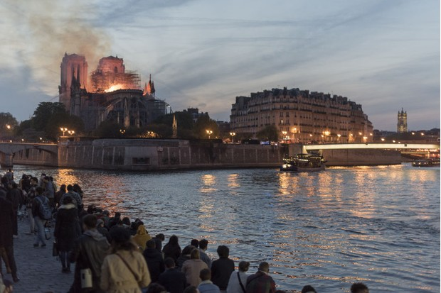 People watch as fire and smoke rise from a fire at Notre-Dame Cathedral. © Martin Barzilai/Bloomberg/Getty