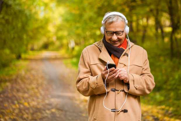 Senior man listening music in park in autumn.
