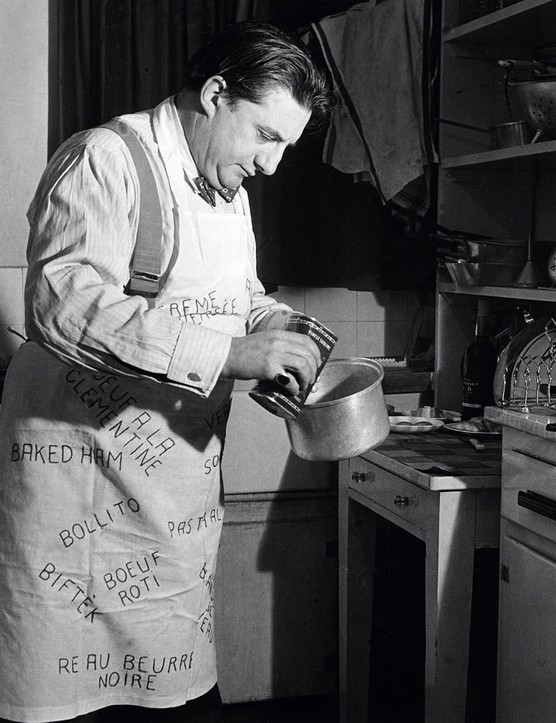 19th August 1954:  British conductor and cellist Sir John Barbirolli (1899 - 1970) cooking in his Manchester flat. The apron covered with the names of his favorite dishes is a gift from friends.  (Photo by Erich Auerbach/Getty Images)