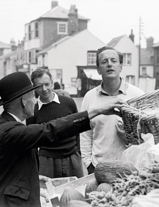 English composer Benjamin Britten (1913 - 1976) buying fruit at a stall in Aldebugh High Street with tenor Peter Pears (1910 - 1986), October 1949. Original Publication : Picture Post - 4896 - An Opera Team Sets To Work - pub. 15th October 1949 (Photo by Kurt Hutton/Picture Post/Hulton Archive/Getty Images)
