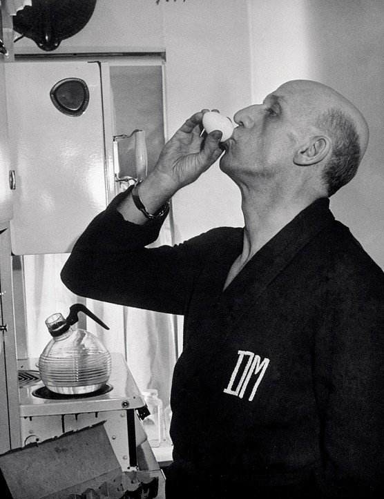 MINNEAPOLIS, UNITED STATES - JANUARY 01:  Conductor Dimitri Mitropoulos sucking raw egg for breakfast in kitchen at home.  (Photo by Alfred Eisenstaedt/The LIFE Picture Collection via Getty Images)