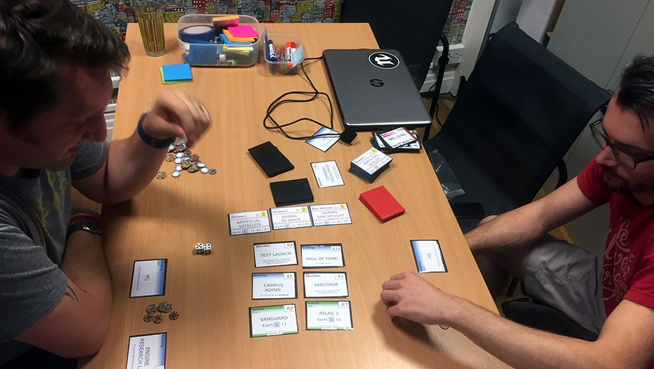 Auroch Digital's Tomas Rawlings (left) and Steve Martin (right) play a card game version of Mars Horizon in their Bristol studio. Reinterpreting the game in this way helps developers experiment with gameplay and test out new ideas.