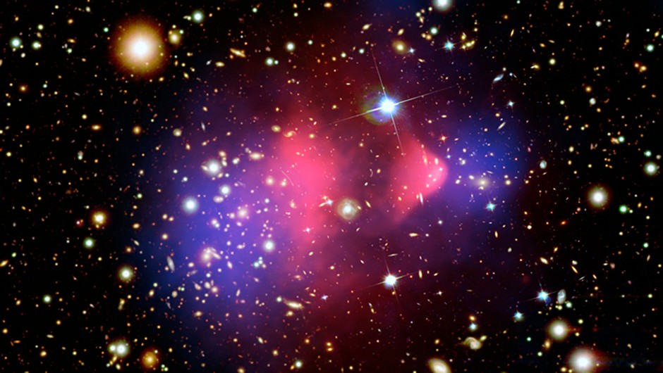 The galaxy cluster 1E 0657-56, known as the Bullet Cluster. Red represents the total visible mass and the blue hues show the distribution of dark matter in the cluster. Credit: NASA/CXC/CfA/M.Markevitch et al