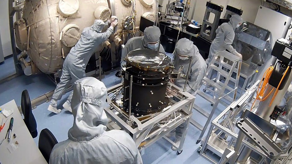 The CHEOPS team at the University of Bern assembles the instrument flight model in the cleanroom. ESA's CHEOPS will study already-known transiting exoplanets in greater detail. Credit: PlanetS