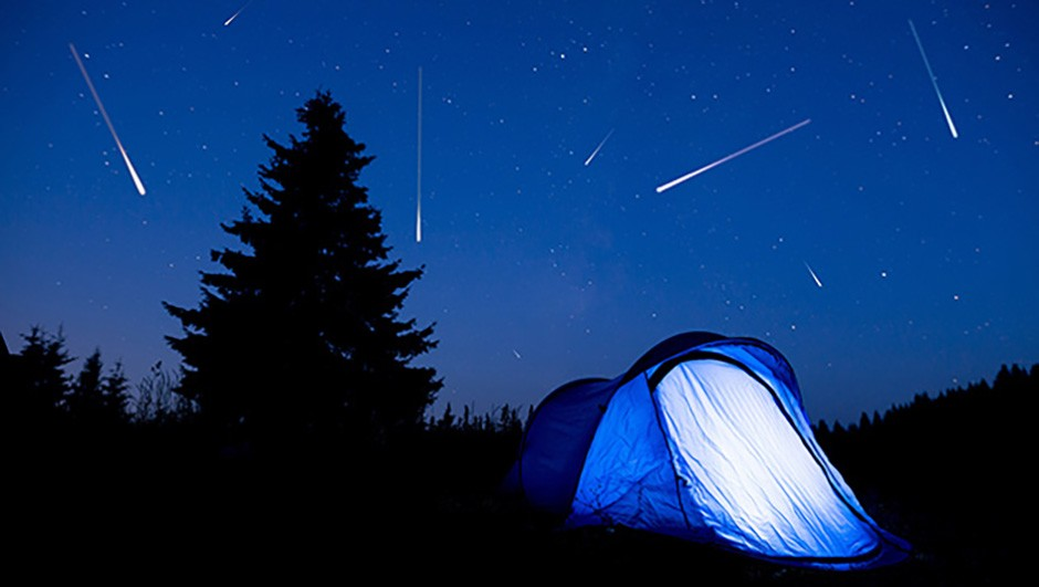 Blue illuminated tent with travelers in the mountain. Background of a pine tree silhouette and the starry summer night sky.
