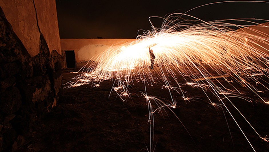 When cloud drifts over, we experiment with light painting with burning wire-wool in a derelict camel farm. © Jamie Carter
