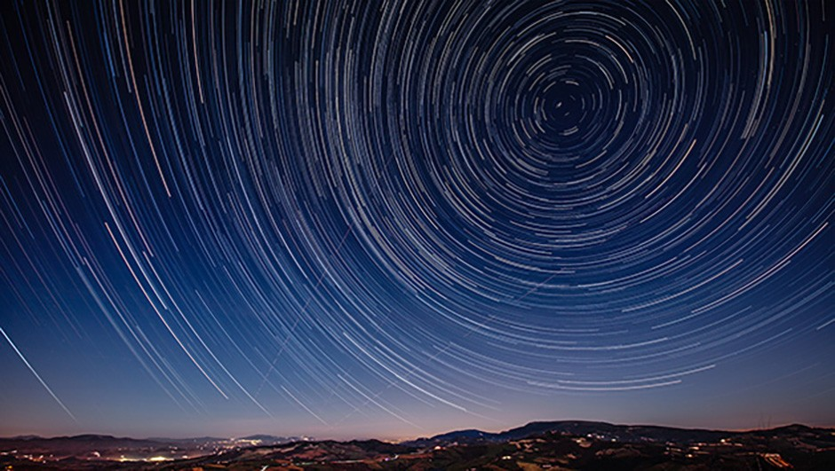 Beautiful track star image during a night in Tuscany. Trajectories of aircraft and shooting stars in the sky. Long exposure for trails of stars.