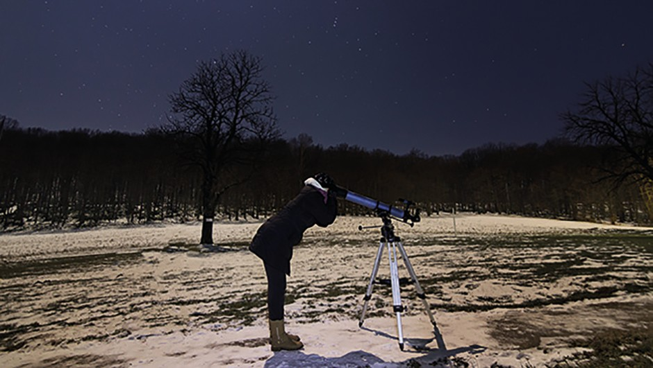 Woman with telescope under winter night sky