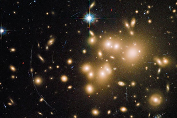A Hubble Space Telescope image showing gravitational lensing in action. At the centre of the image is a galaxy cluster, which contains so much dark matter mass its gravity is bending the light of more distant objects (seen as curves of light around the cluster). Image Credit: NASA, ESA, J. Richard (CRAL) and J.-P. Kneib (LAM). Acknowledgement: Marc Postman (STScI)