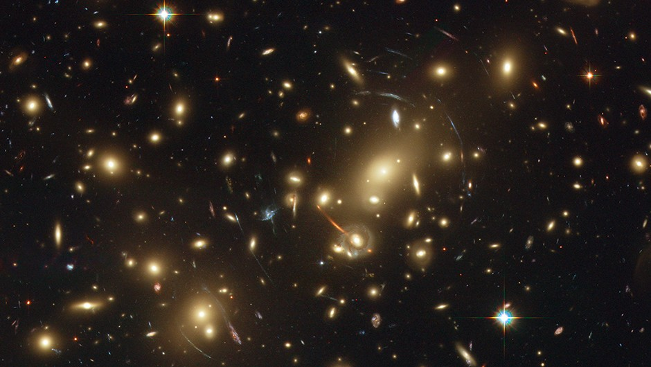 The picture shows Abell 2218, a rich galaxy cluster composed of thousands of individual galaxies. It sits about 2.1 billion light-years from the Earth (redshift 0.17) in the northern constellation of Draco. When used by astronomers as a powerful gravitational lens to magnify distant galaxies, the cluster allows them to peer far into the Universe. However, it not only magnifies the images of hidden galaxies, but also distorts them into long, thin arcs. Several arcs in the image can be studied in detail thanks to Hubble's sharp vision. Multiple distorted images of the same galaxies can be identified by comparing the shape of the galaxies and their colour. In addition to the giant arcs, many smaller arclets have been identified.