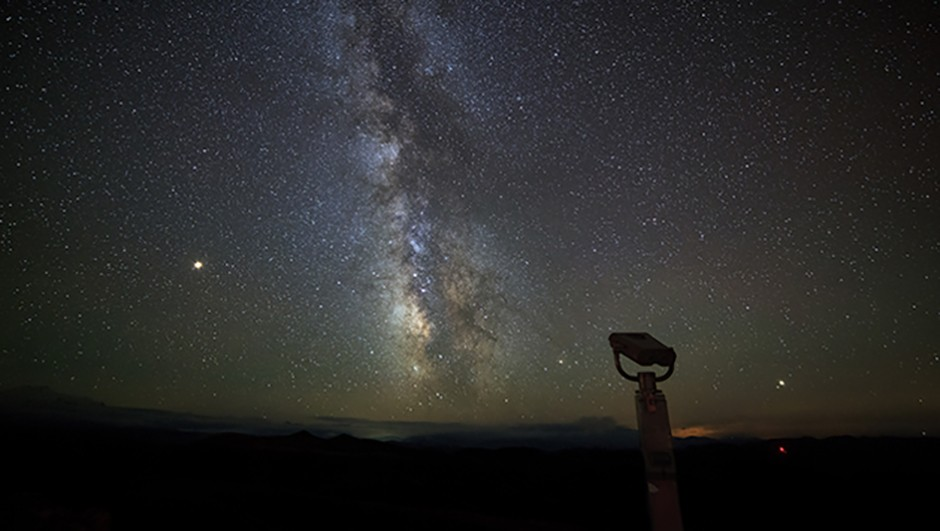 Starry night sky over the mountains of the North Caucasus. Binoculars for travelers to observe the stars of the Milky Way. Summer evening twilight time.