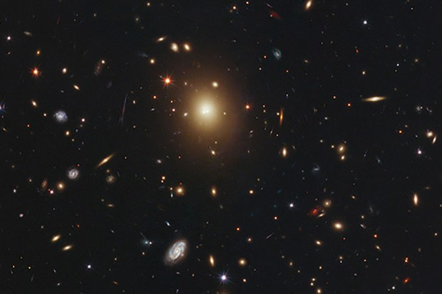 The  giant elliptical galaxy in the centre of this image, taken by the  NASA/ESA Hubble Space Telescope, is the most massive and brightest  member of the galaxy cluster Abell 2261. Astronomers refer to it as the brightest cluster galaxy (BCG). Spanning a little over one million light-years, the galaxy is about 20 times the diameter of  our Milky Way galaxy. Astronomers  used Hubble's Advanced Camera for Surveys and Wide Field Camera 3 to  measure the amount of starlight across the galaxy, catalogued as 2MASX  J17222717+3207571 but more commonly called A2261-BCG (short for Abell  2261 brightest cluster galaxy). Abell 2261 is located three billion  light-years away. The  observations were taken between March and May 2011. The Abell 2261  cluster is part of a multi-wavelength survey called the Cluster Lensing  And Supernova survey with Hubble (CLASH).