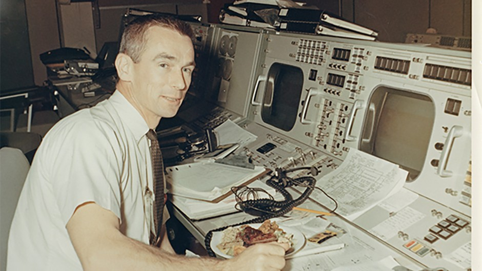 Gene Cernan, who would eventually become the last of the Apollo astronauts to set foot on the Moon, grabs a rare moment of sustenance amongst the hubbub of Mission Control.