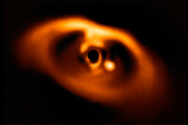 An image of the newborn planet and its host star. The dark circle at the centre is a mask that blocks the light of the central star so astronomers can see the fainter disc and planet. The planet is the bright spot to the right of the black circle. Image Credit: ESO/A. Müller et al.