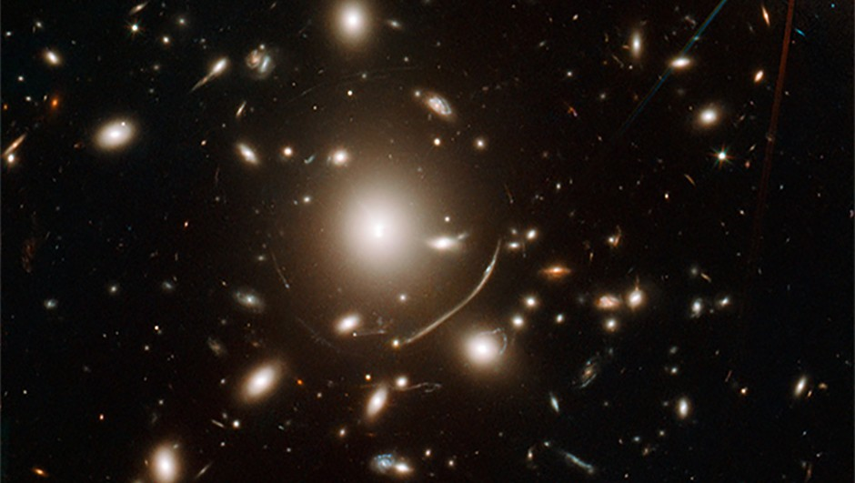 The swirls of light surrounding giant galaxy cluster Abell 383 at the centre of this image show gravitational lensing in action: the effects of massive objects on space-time.Credit: NASA, ESA, J. Richard (CRAL) and J.-P. Kneib (LAM). Acknowledgement: Marc Postman (STScI)