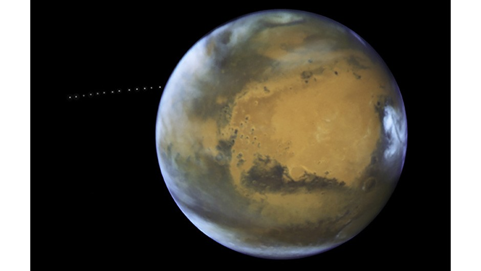Phobos photobomb: this image of the moon Phobos orbiting Mars was captured by the Hubble Space Telescope on 12 May 2016.Phobos's orbit takes it closer to Mars by 2 metres every one hundred years. Scientists estimate the moon will be torn apart by this process in about 30-50 million years. Copyright NASA, ESA and Z. Levay (STScI) Acknowledgment: J. Bell (ASU) and M. Wolff (Space Science Institute)