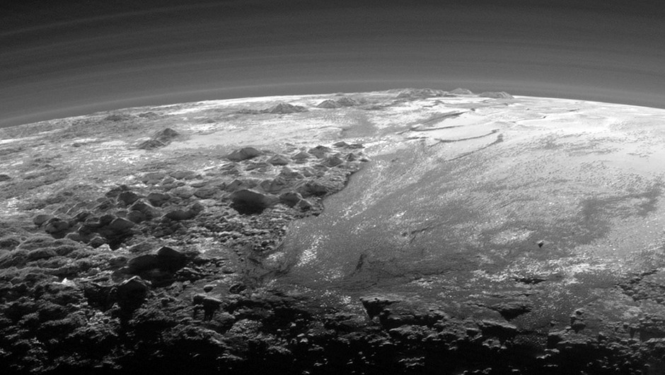 Just 15 minutes after its closest approach to Pluto on July 14, 2015, NASA's New Horizons spacecraft looked back toward the sun and captured a near-sunset view of the rugged, icy mountains and flat ice plains extending to Pluto's horizon. The smooth expanse of the informally named Sputnik Planum (right) is flanked to the west (left) by rugged mountains up to 11,000 feet (3,500 meters) high, including the informally named Norgay Montes in the foreground and Hillary Montes on the skyline. The backlighting highlights more than a dozen layers of haze in Pluto's tenuous but distended atmosphere. The image was taken from a distance of 11,000 miles (18,000 kilometers) to Pluto; the scene is 230 miles (380 kilometers) across. Image Credit: NASA/Johns Hopkins University Applied Physics Laboratory/Southwest Research Institute