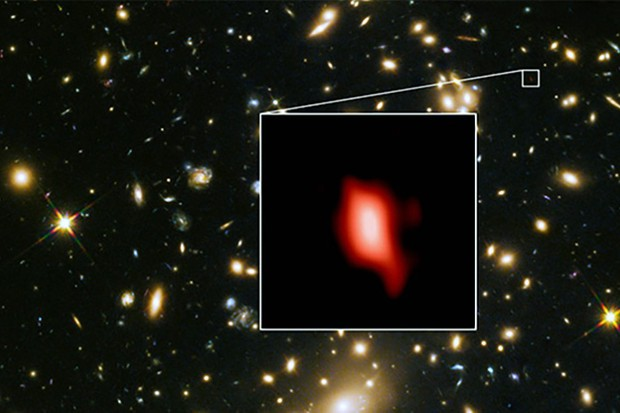 Galaxy cluster MACS J1149.5+2223 in an image captured with the Hubble Space Telescope. Inset is galaxy MACS1149-JD1, seen by ALMA as it existed 13.3 billion years ago. Red shows the distribution of oxygen; the most distant ever detected. Image Credit: ALMA (ESO/NAOJ/NRAO), NASA/ESA Hubble Space Telescope, W. Zheng (JHU), M. Postman (STScI), the CLASH Team, Hashimoto et al.