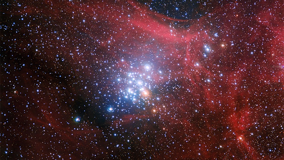 In this image from the Wide Field Imager on the MPG/ESO 2.2-metre telescope at ESO's La Silla Observatory in Chile young stars huddle together against a backdrop of clouds of glowing gas and lanes of dust. The star cluster, known as NGC 3293, would have been just a cloud of gas and dust itself about ten million years ago, but as stars began to form it became the bright group we see here. Clusters like this are celestial laboratories that allow astronomers to learn more about how stars evolve.