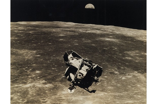 Apollo 11's lunar module passes over the surface of the Moon; Earth rising over the limb.