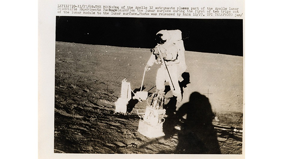 An Apollo 12 astronaut places part of the Apollo Lunar Scientific Experiments Package on the surface of the Moon.
