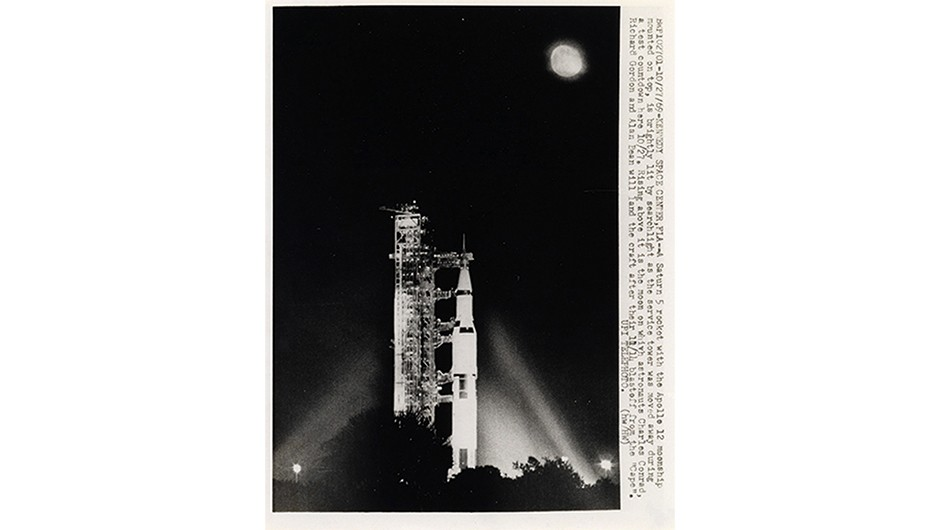 A Saturn V rocket illuminated by spotlight as the service tower is moved away during a countdown in preparation for Apollo 12.