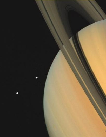 Saturn and two of its moons photographed in 1980 by Voyager 1. The moons, Tethys (closest to the planet) and Dione, are visible as bright spots in space next to the gas giant. Tethys's shadow can also be seen on Saturn itself. (Credit: NASA/JPL)