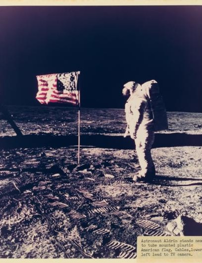 Buzz Aldrin stands beside the US flag on the lunar surface.