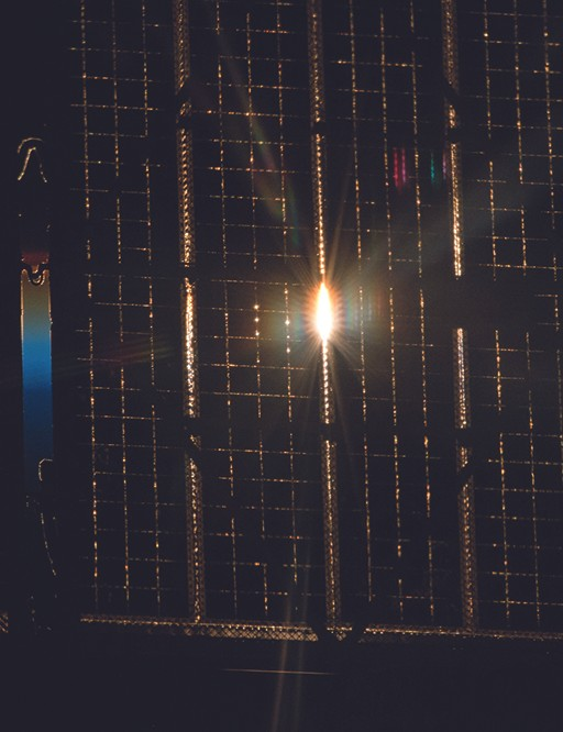 The setting Sun peeks through the solar arrays of the Russian Soyuz spacecraft.