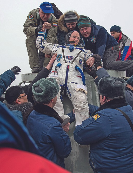 Being pulled out of the Soyuz by the Russian rescue forces after a year in space.