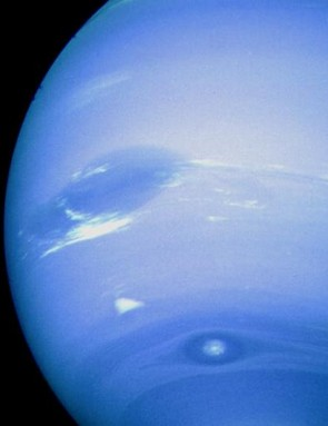 Voyager 2 photograph of Neptune. The Great Dark Spot is dominant close to the left limb, while immediately below it is a white feature nicknamed 'Scooter'. Near the bottom of the planet's disc is Dark Spot 2, with its light core. These features are rarely seen in close proximity due to their different rotational speeds. (Credit: NASA/JPL)