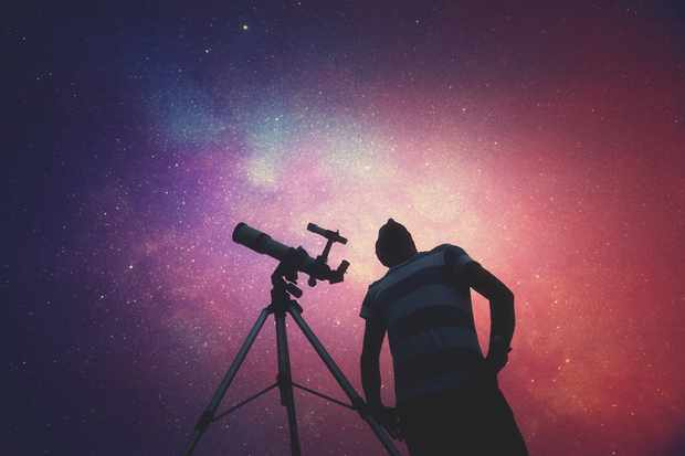 Man looking at the stars with telescope beside him. Credit: iStock