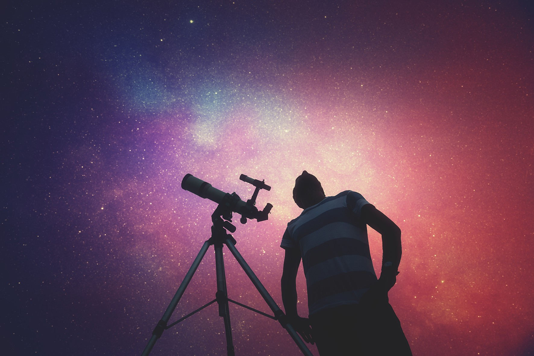 Man looking at the stars with telescope beside him. Milky Way stars are my astronomy work, no elements of NASA or other third party.
