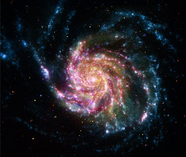 This image of the Pinwheel Galaxy, or M101, combines data in the infrared, visible, ultraviolet and x-rays from four of NASA's space telescopes. This multi-spectral view shows that both young and old stars are evenly distributed along M101's tightly-wound spiral arms. Such composite images allow astronomers to see how features in one part of the spectrum match up with those seen in other parts. It is like seeing with a regular camera, an ultraviolet camera, night-vision goggles and X-Ray vision, all at once! The Pinwheel Galaxy is in the constellation of Ursa Major (also known as the Big Dipper). It is about 70% larger than our own Milky Way Galaxy, with a diameter of about 170,000 light years, and sits at a distance of 21 million light years from Earth. The red colors in the image show infrared light, as seen by the Spitzer Space Telescope. These areas show the heat emitted by dusty lanes in the galaxy, where stars are forming. The yellow component is visible light, observed by the Hubble Space Telescope. Most of this light comes from stars, and they trace the same spiral structure as the dust lanes seen in the infrared. The blue areas are ultraviolet light, given out by hot, young stars that formed about 1 million years ago. The Galaxy Evolution Explorer (GALEX) captured this component of the image. Finally, the hottest areas are shown in purple, where the Chandra X-ray observatory observed the X-ray emission from exploded stars, million-degree gas, and material colliding around black holes. Credit: NASA/JPL