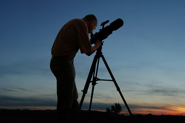 Man looking through telescope. Credit: Panther Media GMBH/Alamy Stock Photo