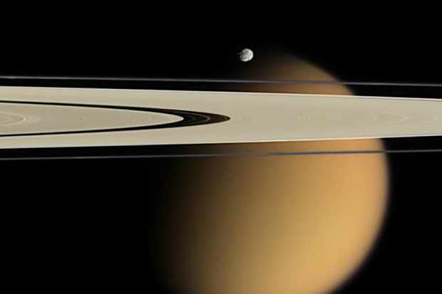 A Cassini image showing Titan, Saturn's largest moon, behind the planet's rings. The smaller moon Epimetheus can be seen in the foreground. Image Credit: NASA/JPL/Space Science Institute