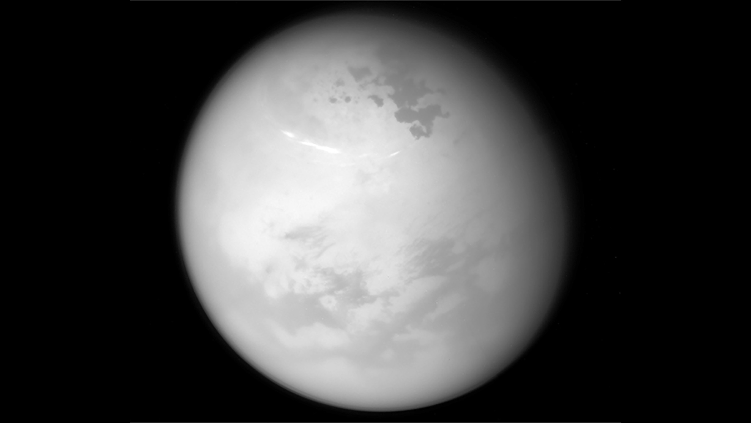 Methane clouds drift across Titan's summer skies in this Cassini image. The darker patches are hydrocarbon lakes.Credit: NASA/JPL-Caltech/Space Science Institute