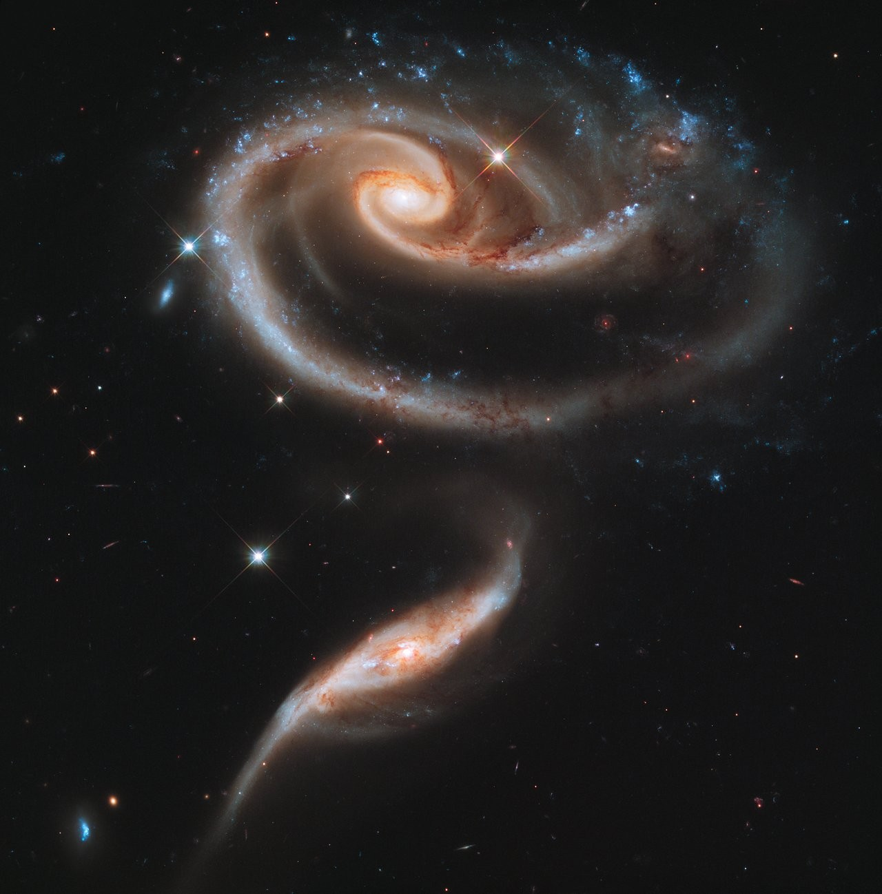 This image of a pair of interacting galaxies called Arp 273 was released to celebrate the 21st anniversary of the launch of the NASA/ESA Hubble Space Telescope. The distorted shape of the larger of the two galaxies shows signs of tidal interactions with the smaller of the two. It is thought that the smaller galaxy has actually passed through the larger one.