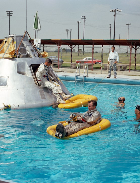 Poolside training, June 1966. The crew of Apollo 1 practice water egress training at Ellington Air Force Base, Houston, Texas. On the life raft in the foreground is astronaut Edward H White II. Roger B Chaffee can be seen climbing out of the boilerplate spacecraft, whilst Virgil I Grissom is still inside. Credit: NASA