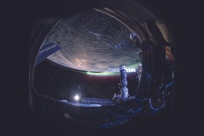From the cupola, I caught a fish-eye view of the aurora looking like a green-and-red aircraft contrail.