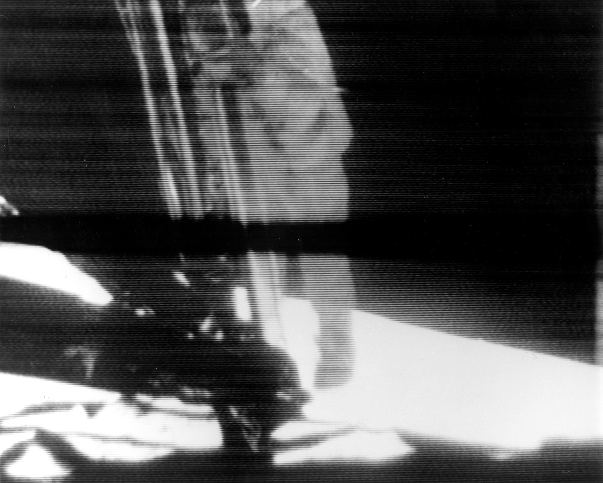 A reproduction of the television image that was broadcast to the world on 20 July. Neil Armstrong is seen descending the Lunar Module ladder, ready to set foot on the surface of the Moon. The black bar across the centre of the image is caused by an anomaly in the TV Ground Data System at Goldstone Tracking Station. Credit: NASA