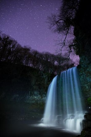 Irresistible - Andrew Whyte, Taken at the Dark Sky site of the Brecon Beacons, the image shows the Sgwd yr Eira Waterfall in the National Park gleaming under the night sky. The photographer was able to position his camera on one side of the river, cross behind the waterfall and trigger the camera from the other side of the river using only his phone meaning he could use just the right amount of light to gently illuminate the landscape.