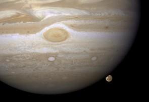 Jupiter's moon Ganymede can just be seen poking out from behind the giant planet. Credit: NASA/ESA/E. Karkoschka (University of Arizona)