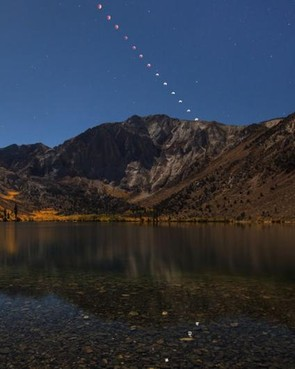 Lunar Eclipse setting over Convict Lake - Jeff Sullivan, The landscape around Convict Lake was well lit by the moonlight as the Lunar eclipse started when the photographer took the image. He then captured the moon at roughly 8 minute intervals thereafter and merged the sequential images into the original exposure using StarStaX. A second camera was used to test exposure so the main camera could be adjusted as the moon dimmed.